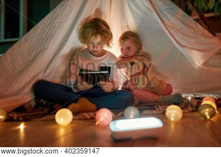 Adorable Boy Using Tablet Pc While Spending Time With His Little Sister, Sitting On A Blanket In A H