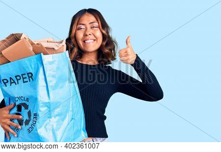 Young beautiful mixed race woman holding recycling wastebasket with paper and cardboard smiling happy and positive, thumb up doing excellent and approval sign