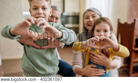 Love Your Family. Happy Grandparents With Grandchildren Making Heart Sign With Hands And Smiling At