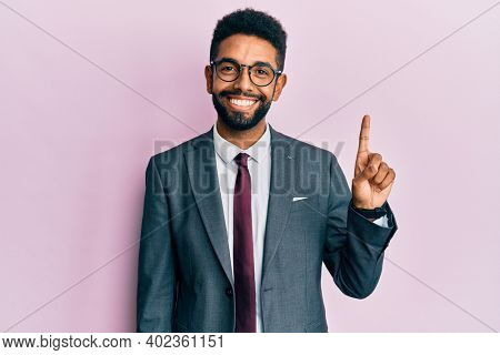Handsome hispanic business man with beard wearing business suit and tie showing and pointing up with finger number one while smiling confident and happy.