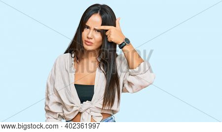 Young beautiful hispanic girl wearing casual clothes pointing unhappy to pimple on forehead, ugly infection of blackhead. acne and skin problem
