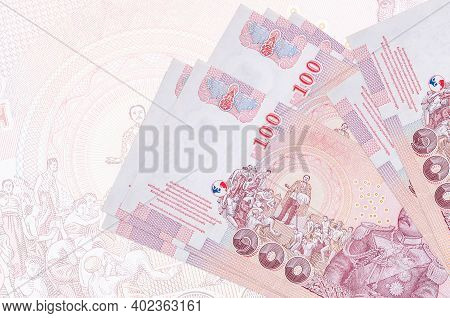 100 Thai Baht Bills Lies In Stack On Background Of Big Semi-transparent Banknote. Abstract Presentat