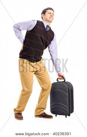 Full length portrait of a man lifting his luggage and suffering from a back pain isolated on white background