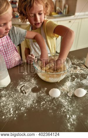 High Angle View Of Little Siblings, Boy And Girl In Aprons Preparing Dough For Cookies Together On T