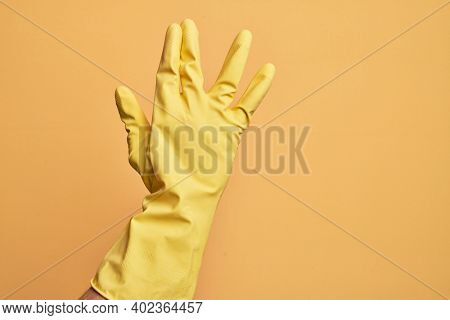 Hand of caucasian young man with cleaning glove over isolated yellow background greeting doing Vulcan salute, showing back of the hand and fingers, freak culture