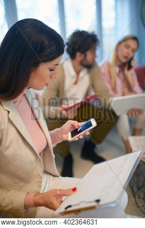 A group of young business people at a meeting in a relaxed atmosphere in an apartment taking a break after hard work. Business, meeting, people