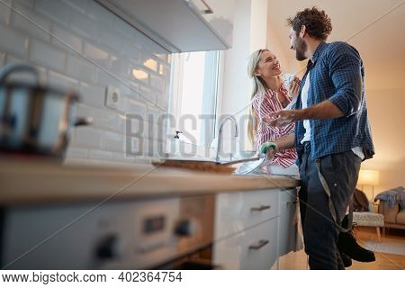 A young man is happy helping about housework in a relaxed atmosphere in the kitchen. Kitchen, housework, home, relationship