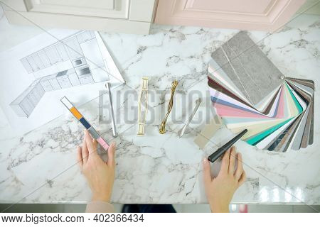 Home Improvement Concept. Girl The Designer Chooses The Facades And Handles For Cabinet Furniture In