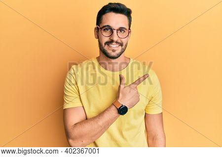 Young hispanic man wearing casual clothes and glasses cheerful with a smile of face pointing with hand and finger up to the side with happy and natural expression on face