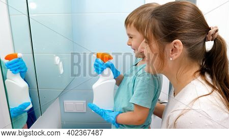 Smiling Little Boy Applying Chemical Detergent And Spraying Cleanser Spray On Mirror While Helping M