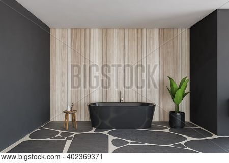 Black And Wooden Bathroom With Bathtub And Table With Plant. Bathtub Against Wooden Wall On Grey Flo