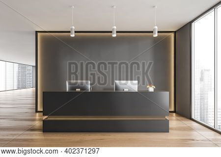 Black And Wooden Reception Room With Two Computers And Armchairs. Black Wall With Yellow Backlight,