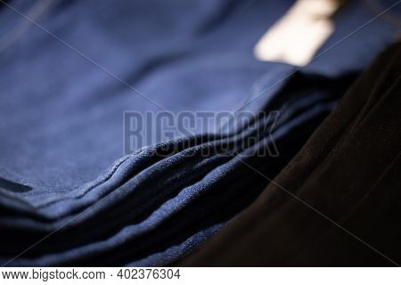 Stack Of Blue And Black Jeans In A Shop. Concept Of Buy, Sell, Shopping And Jeans Fashion.