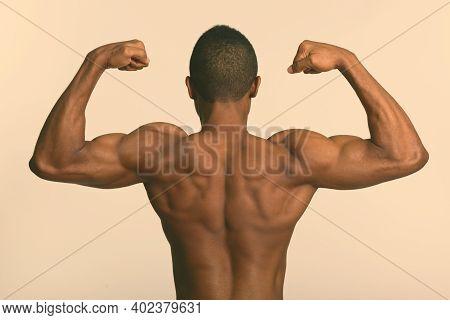 Young Muscular African Man Shirtless Flexing Both Arms