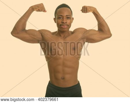 Young Muscular African Man Flexing Both Arms