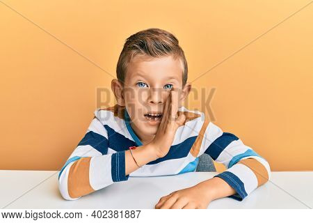 Adorable caucasian kid wearing casual clothes sitting on the table hand on mouth telling secret rumor, whispering malicious talk conversation