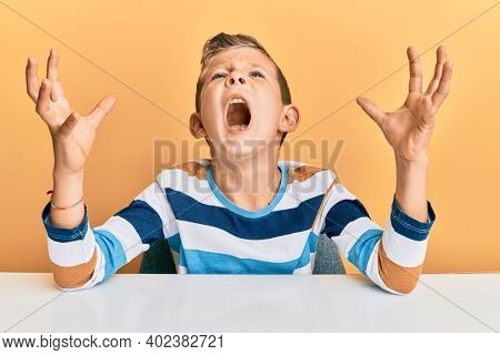 Adorable caucasian kid wearing casual clothes sitting on the table crazy and mad shouting and yelling with aggressive expression and arms raised. frustration concept.