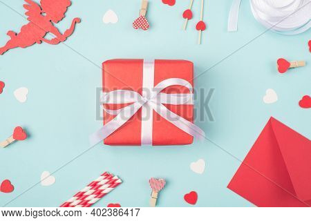 Surprise On Valentines Day Concept. Above Close Up View Photo Of Wrapped Package Giftbox With Cupid