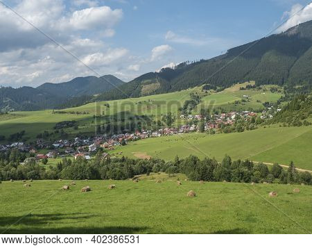 View On Village Liptovska Luzna At The Foothills Of Low Tatras Mountains With Lush Green Meadow, For