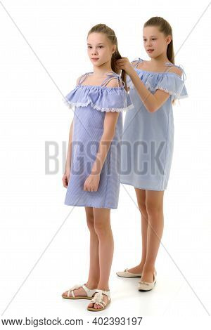 Girl Braiding Braids For Her Sister, Two Pretty Twin Sisters In Identical Light Dresses Standing One