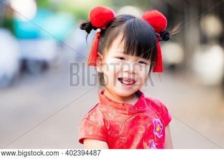 Closeup, The Girl Shows A Pretty Cheeky Face. Happy Child In Chinese New Year. Beautiful Kid Wore A