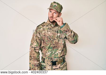Young caucasian man wearing camouflage army uniform mouth and lips shut as zip with fingers. secret and silent, taboo talking