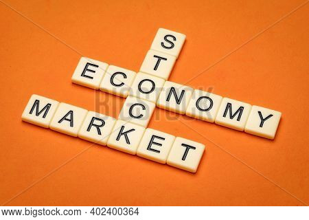 stock market and economy crossword in ivory letter tiles against textured handmade paper, bsuiness and finance concept