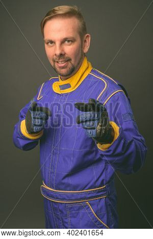 Blond Bearded Man Motorcyclist With Goatee In Full Gear Against Gray Background
