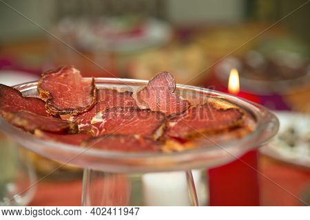 Close-up Of Red Slices Of Iberian Loin On Glass Dish And Multicolored Background