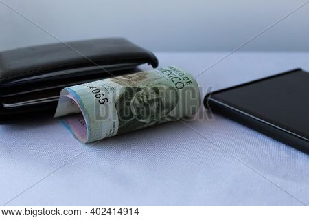 Mexican Money, Black Leather Wallet And Smartphone Corner On The Table