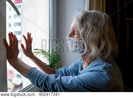 Lonely Old Woman In A Medical Mask Looks Out The Window During The Lockdown. A Depressed Lady At Hom
