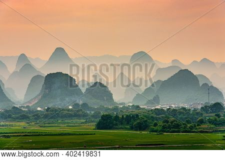Guilin, China karst mountain landscape at dusk.