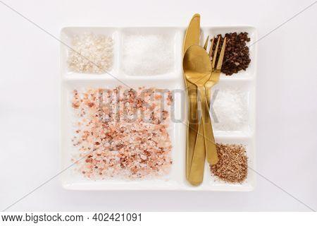 Six Varieties Of Salt On A Plate With Silverware .