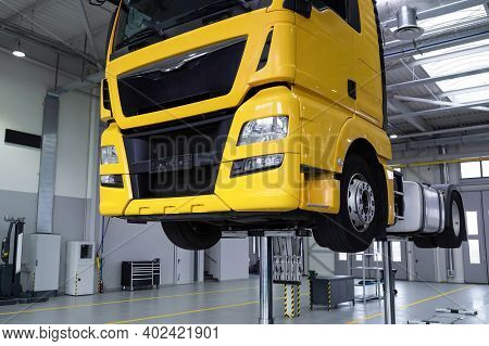 Yellow Truck On A Lift In A Car Service. Servicing And Repairing Trucks In A Large Garage. Car Servi