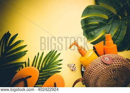 Sunscreen Bottles Arranged In Straw Bag On A Bright Yellow Background With Palm Leaves, Top View