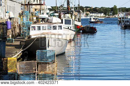 Portland, Maine, Usa - 25 July 2019: Lobster Fishing Boats Docked Behind Stores In A Canal In Porlan