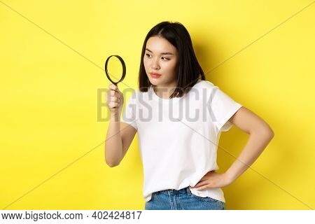 Asian Woman Detective Looking Through Magnifying Glass With Intrigued Look, Found Clues, Standing Ov
