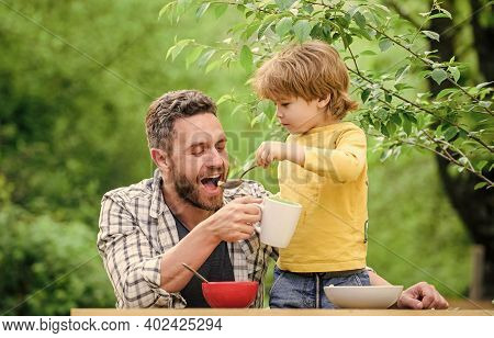 Family Enjoy Homemade Meal. Food Habits. Little Boy With Dad Eating Food Nature Background. Summer B