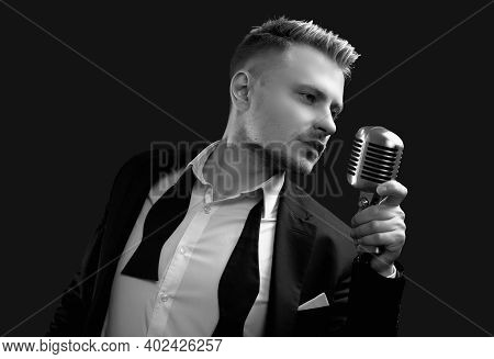 Handsome Singer In Elegant Tuxedo And Bow Tie With Vintage Microphone
