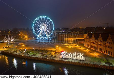 Gdansk, Poland - January 1, 2021: Amazing cityscape over Motlawa river with Gdansk city sign at dusk, Poland