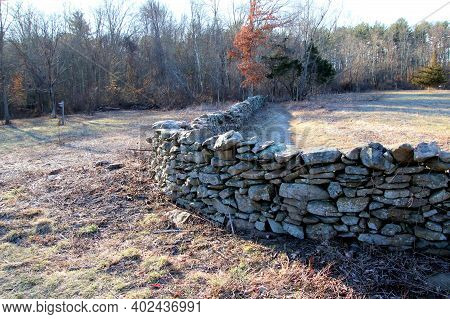 Long Curved Stonewall Dividing Two Open Fields.