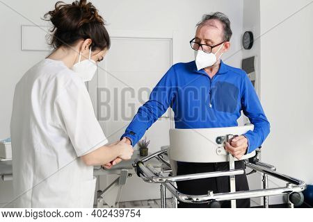 Female Nurse Caregiver, Holding Patient Hand, Support Disabled Patient Sit On Wheelchair At Hospital