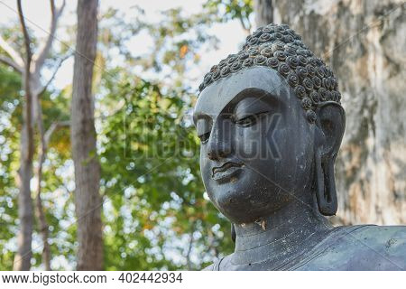 Phayao, Thailand - Dec 6, 2020: Headshot Front Left Buddha Statue Giving The Firts Sermon On Green F