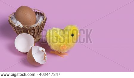 Cute Toy Chicken Creacking From Eggshell On Pink Background.  Chick Hatching From Cracked Chick Egg.