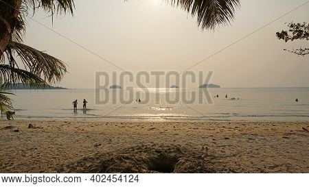 Smog Obscures The Suns Rays. People Relax On The Beach. Yellow Rays Of Light. View Of The Islands, S