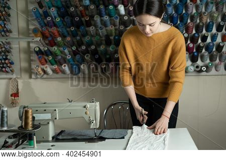 A Dressmaker Stands At A Work Table And Cuts White Fabric Along A Pattern With Scissors. The Seamstr