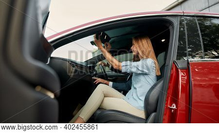 Young Caucasian Woman Examining Interior Of New Car While Sitting On Front Passenger Seat Beside Man