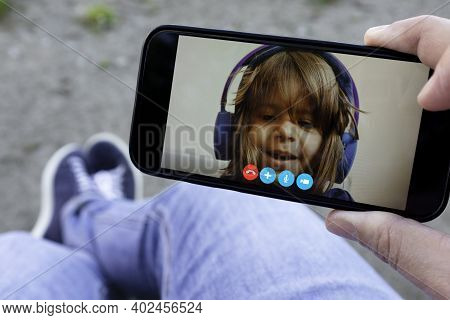 Father And Daughter Talking To Each Other Through A Video Call On A Smartphone - Hand Holding A Smar