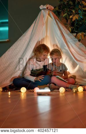 Two Little Kids, Boy And Girl Telling Stories To Each Other While Sitting On A Blanket In A Teepee M