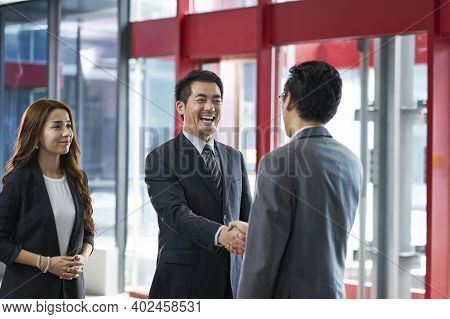 Asian Corporate Executives Shaking Hands With Visiting Client In Elevator Hall Of Modern Office Buil